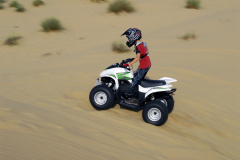 Young boy quad biking in the dunes